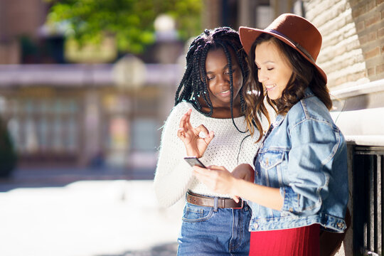 Two friends looking at their smartphone together. Multiethnic women.