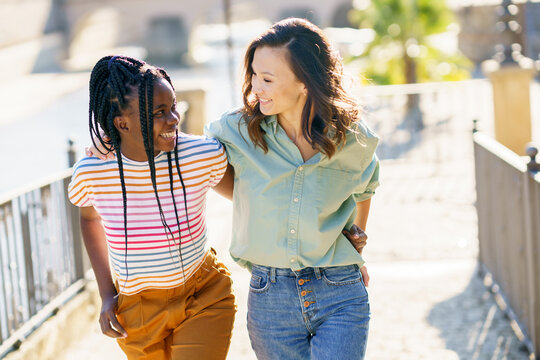 Two friends talking together on the street. Multiethnic women.