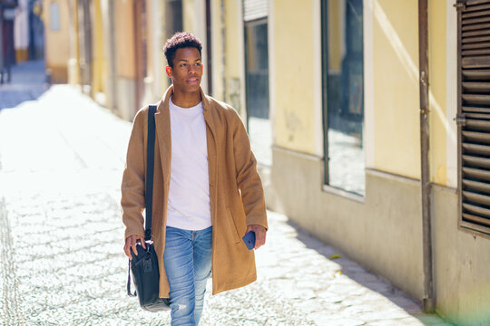Young black man walking down the street carrying a briefcase and a smartphone.