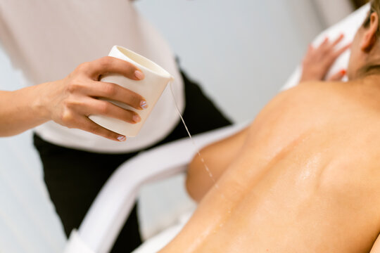 Beauty salon professional pouring oil from a massage candle on the back of his patient.