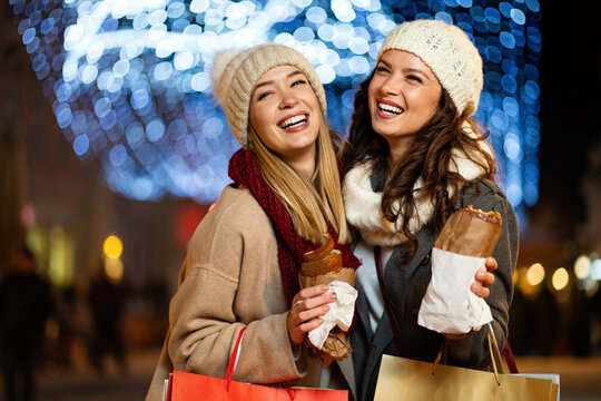 Portrait of happy women enjoying christmas fair and shopping together outdoors.