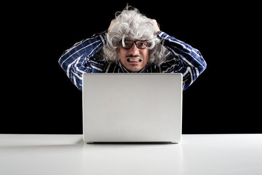 Portrait of a stressed senior man working on a laptop computer