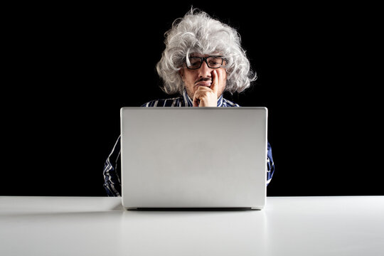 An elder serious man lost in thoughts in front of a laptop computer,
