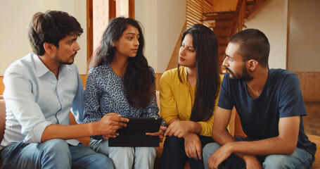 Fototapeta Group of Indian friends sitting in a living room, discussing a matter with a tablet obraz