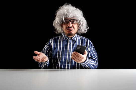 A bewildered senior does not understand how to use the smartphone