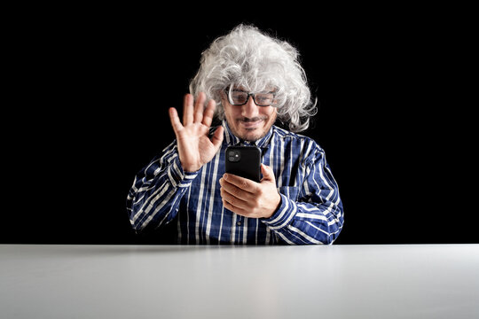 Smiling man sitting at the desk having a videochat