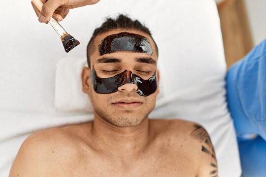 Latin man reciving facial treatment at beauty center.