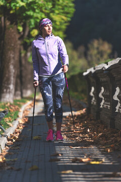 A woman relaxes by practicing Nordic walking