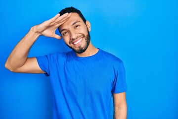 Obraz Hispanic man with beard wearing casual blue t shirt very happy and smiling looking far away with hand over head. searching concept. - fototapety do salonu