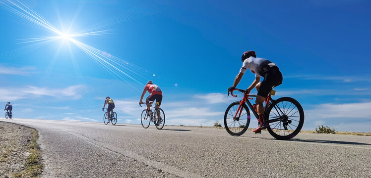 Cycling race on an uphill road in Ioannina, Greece, four bikers and bikes  sun