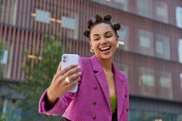 Positive carefree girl with toothy smile takes selfie on smartphone poses against modern urban building dressed in stylish pink jacket records video and talks with followers. Adolescence technology