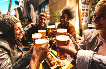 Obraz Happy friends drinking beer at brewery bar out doors on night mood - Friendship lifestyle concept with young people enjoying time together at open air pub - Warm dark filter with focus on glasses - fototapety do salonu