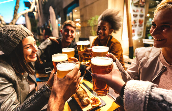 Happy friends drinking beer at brewery bar out doors on night mood - Friendship lifestyle concept with young people enjoying time together at open air pub - Warm dark filter with focus on glasses