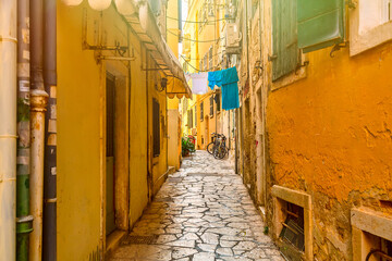 Kerkyra city narrow street view with yellow colorful houses and bikes during sunny day. Corfu Island, Ionian Sea, Greece.