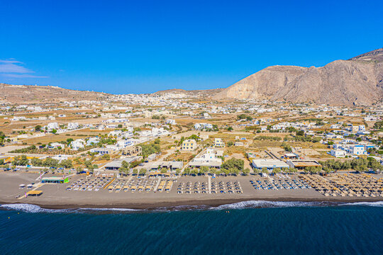 Top view aerial drone photo of black Perissa beach with beautiful turquoise water, sea waves and straw umbrellas. Vacation travel background. Aegean sea, Santorini Island, Greece