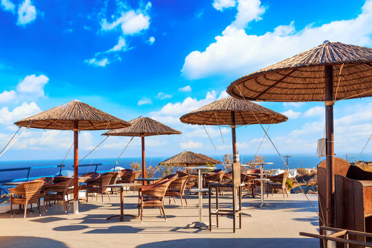 Restaurant with straw umbrellas in Oia village on Santorini island, Aegean sea, Greece.