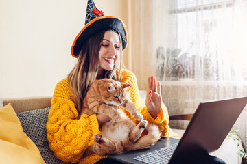 Obraz Halloween lockdown. Woman in witch hat holding cat waving hi in video chat on laptop. Holidays during coronavirus - fototapety do salonu