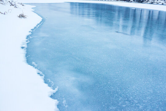 frozen river covered with ice. snow on the shore. beautiful winter nature background