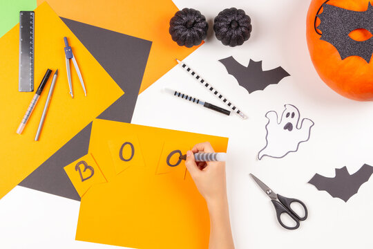 Preparing for Halloween. Teenage kid hands drawing, cutting colored paper and making Halloween party decorations on white table at home. Top view