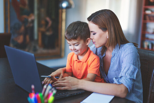 Tired woman holding head to son, while he typing on laptop
