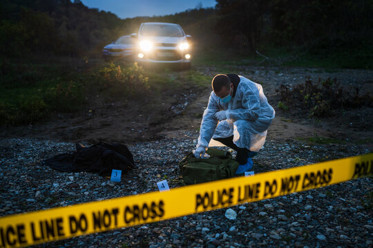 Forensic police investigator collecting evidence at the crime scene in nature at night