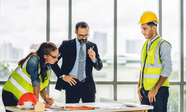 Professional of team architect industrial engineer cargo foreman in helmet working new construction project architectural plan with blueprint and construction tool on table at the building site