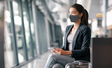 Obraz Travel during coronavirus. Asian business woman wearing face mask in airport terminal waiting for flight thinking looking out the window using phone app for vaccine passport. - fototapety do salonu