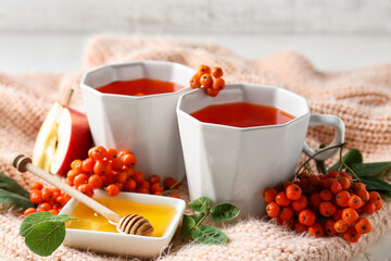 Obraz Composition with cups of tasty rowan tea, berries and honey on table, closeup - fototapety do salonu