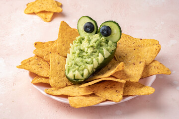 Obraz Funny alligator avocado bowl guacamole dip and nachos - fototapety do salonu