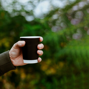 The man hand holding a blank paper cup in a wooded landscape background. Autumn lifestyle. Coffee black cup. Copyspace