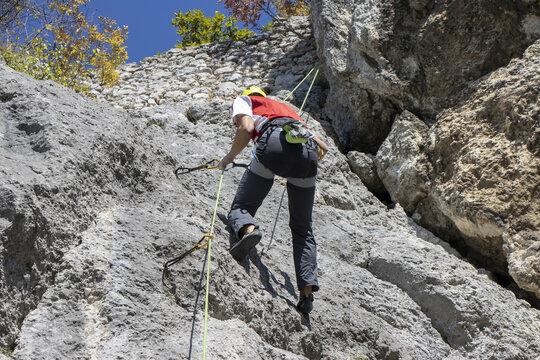 Young man climbing natural high rocky wall