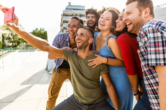 Multiracial young friends taking a selfie photo with mobile phone - Millennial multiethnic group of people having fun together outdoors - Friendship, unity and millennial people concept