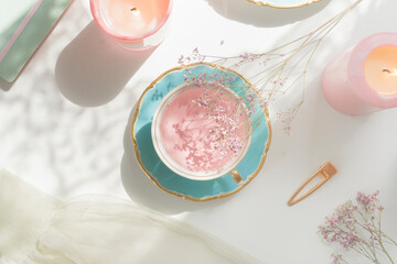 Obraz Pink flower tea in vintage porcelain tea cup, candles, flowers and notebook on white table with natural light. Romantic morning routine with healthy warm drink. Top view. - fototapety do salonu