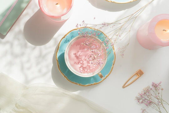 Pink flower tea in vintage porcelain tea cup, candles, flowers and notebook on white table with natural light. Romantic morning routine with healthy warm drink. Top view.