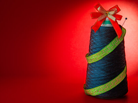 Creative Christmas tree made from coil of green threads, red bow and green ribbon on red paper background with light circle. Merry christmas, new year concept, side view, copy space