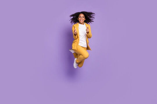 Photo of cheerful positive lady wear yellow suit glasses jumping high pointing fingers you isolated purple color background
