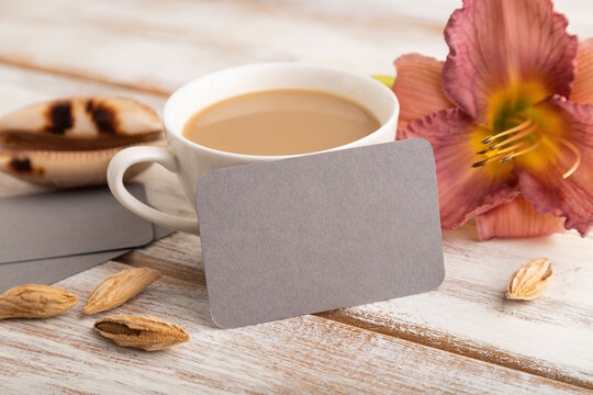 Gray paper business card mockup with purple day-lily flower and cup of coffee on white wooden background.  side view, copy space.