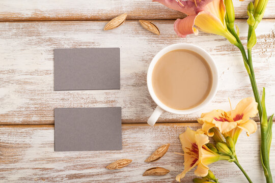 Gray paper business card mockup with orange day-lily flower and cup of coffee on white wooden background.  top view, copy space.