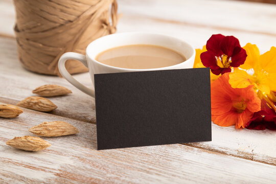 Black paper business card mockup with orange nasturtium flower and cup of coffee on white wooden background.  side view, copy space.