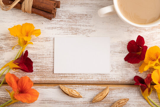 White paper business card mockup with orange nasturtium flower and cup of coffee on white wooden background. top view, copy space.
