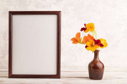 Wooden frame with orange nasturtium flowers in ceramic vase on gray concrete background. side view, copy space.