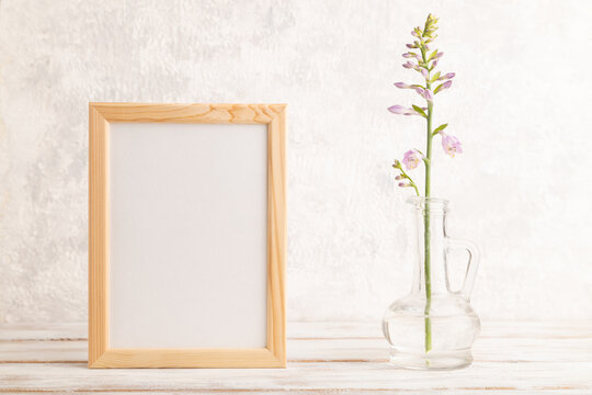 Wooden frame with hosta flowers in glass vase on gray concrete background. side view, copy space.