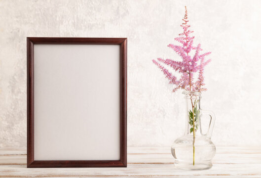 Wooden frame with pink astilbe flowers in glass vase on gray concrete background. side view, copy space.