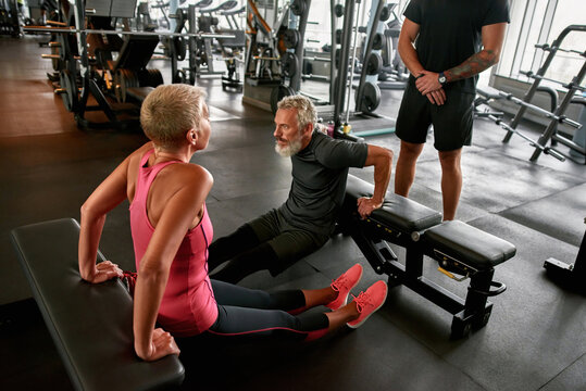 Middle age woman excercising with male friend in gym