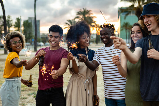 Multicultural united group of young friends having party together with sparkles while drinking beer outdoor - Community, friendship, unity and people celebrating concept - Focus on man on the corner