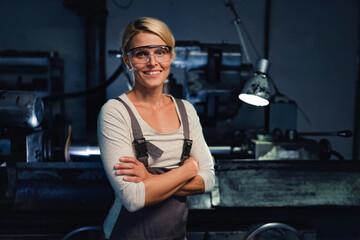 Obraz Portrait of mid adult industrial woman working indoors in metal workshop, looking at camera. - fototapety do salonu