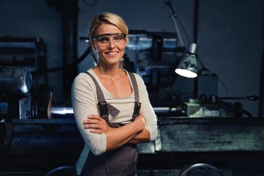 Portrait of mid adult industrial woman working indoors in metal workshop, looking at camera.
