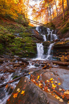 shypot waterfall among the rock in evening light. beautiful autumnal nature scenery in the forest. wet foliage on the stones. popular travel destination of transcarpathia, ukraine
