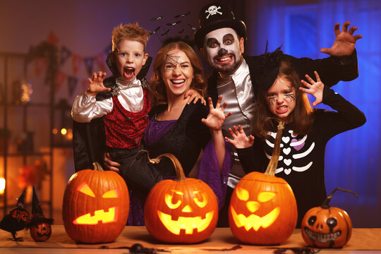 Young caucasian family mother father and children in Halloween costumes and makeup making scary gesture, saying trick or treat while celebrating together all hallows eve in dark room at home
