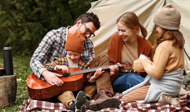 Father, mother and little son sitting near tourist tent and playing guitar during camping